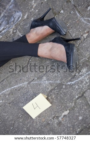 crime scene - outline of female legs and placard on the ground - stock photo