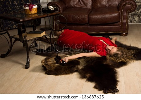 Crime scene simulation: lifeless blonde in the red dress lying on the floor - stock photo