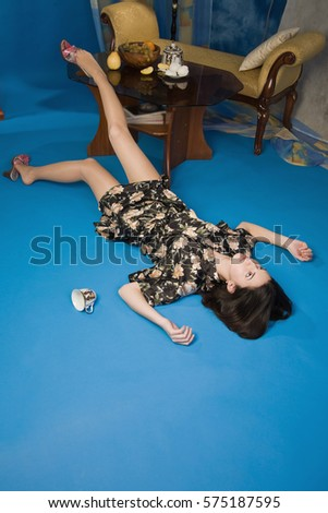 Crime scene simulation: lifeless brunette lying on the floor
