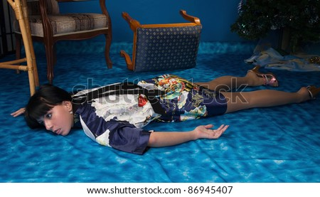 Crime scene simulation: strangled  brunette lying on the floor - stock photo
