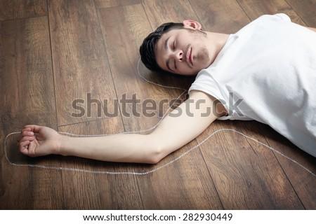 Crime scene simulation, young man lying on floor - stock photo