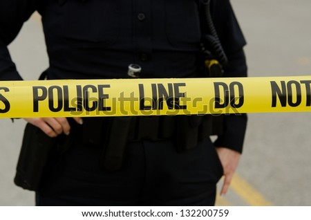 crime scene tape in the street with an officer in the background. - stock photo