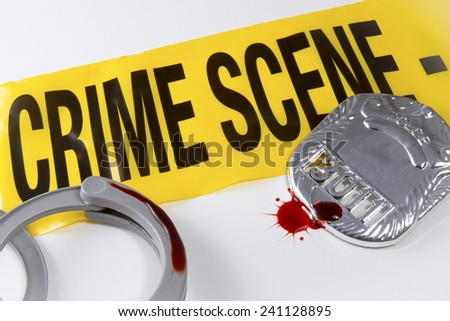 Crime scene tape with blood covered police badge and handcuffs