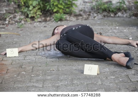 crime scene - young woman lying on a ground with two placards at the sides - stock photo