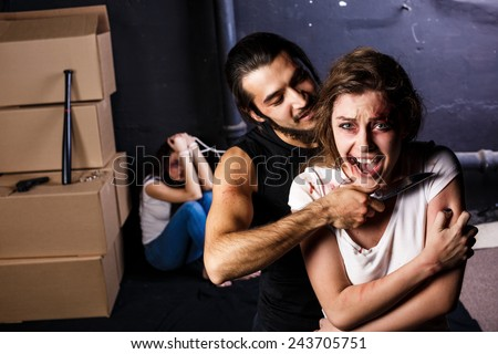 Crime. Two beautiful girls in the Business clothing kidnapped by criminals. Terrorist is threatening hostages with a knife - stock photo