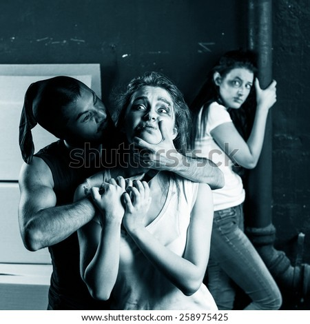 Crime. Two beautiful girls kidnapped by criminals. Terrorist is threatening hostages with a knife - stock photo