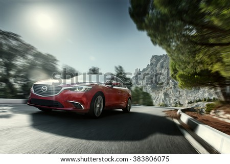 Crimea, Russia - September 20, 2015: Red car Mazda speed driving on asphalt road near mountain at daytime - stock photo