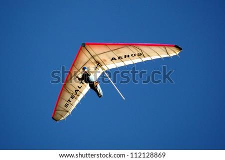 CRIMEA, UKRAINE - SEPTEMBER 4: Competitor Artem Teryohin of the Grininko hang gliding competitions takes part in the Klementieva mountain on September 4, 2012 in Crimea, Ukraine - stock photo