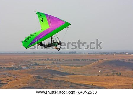 CRIMEA, UKRAINE - SEPTEMBER 9: Competitor of the Grininko hang gliding competitions takes part in the Klementieva mountain on September 9, 2010 in Crimea, Ukraine - stock photo