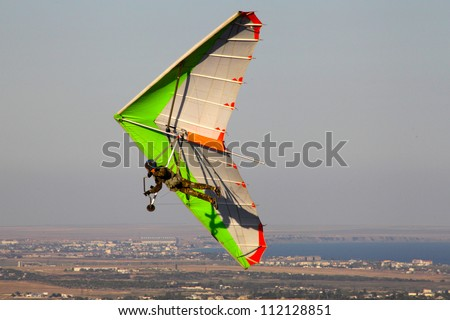 CRIMEA, UKRAINE - SEPTEMBER 4: Competitor  of the  hang gliding competitions takes part in the Klementieva mountain on September 4, 2012 in Crimea, Ukraine - stock photo