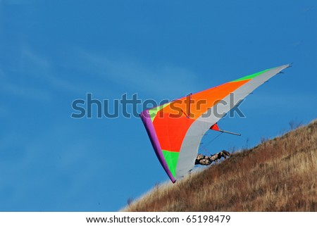 CRIMEA, UKRAINE - SEPTEMBER 9: Competitor of the  hang gliding competitions taking part on the Klementieva mountain on September 9, 2010 in Crimea, Ukraine - stock photo