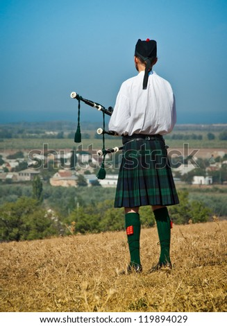 CRIMEA, UKRAINE - SEPTEMBER 29: Landscape with Scottish bagpiper in old military uniform. Historical reenactment of the Alma battle on Crimean War 1854. September 29, 2012 in Crimea, Ukraine. - stock photo