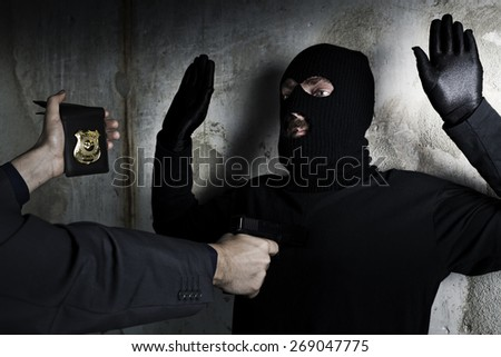 Criminal being arrested by policeman - stock photo
