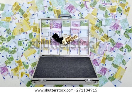 Criminal concept: Gold gun revolver and briefcase full of counterfeit money. Case full of euro banknotes on money background.  - stock photo