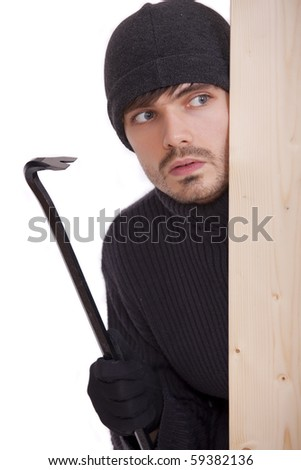criminal guy with crowbar hiding behind wooden bar - stock photo