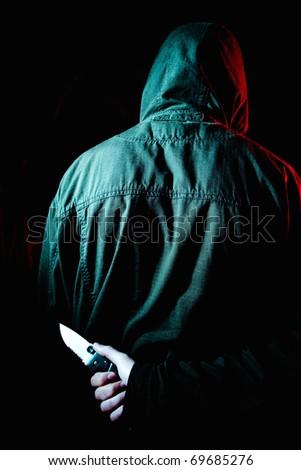 Criminal holding knife behind his back - stock photo