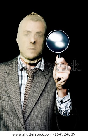 Criminal in a smart business suit and stocking mask holding up a large magnifying glass in a Criminal Investigation concept, studio portrait on black - stock photo