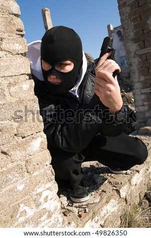 Criminal in black balaclava mask waiting for a victim round the corner - stock photo