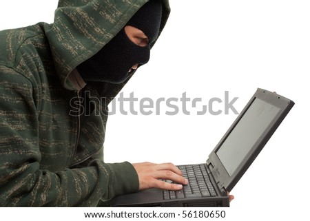 criminal in black clothes and balaclava with the laptop
