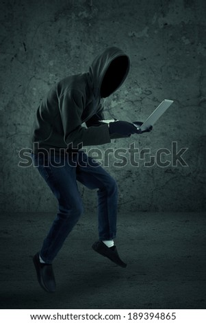 Criminal in dark clothes and balaclava with the laptop - stock photo