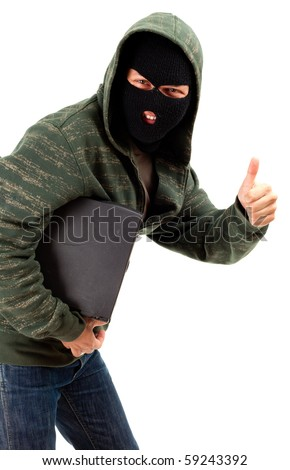 criminal in dark clothes and balaclava with the laptop, thumb up - stock photo