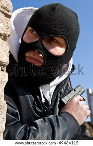 Criminal in mask waiting for a victim round the corner - stock photo