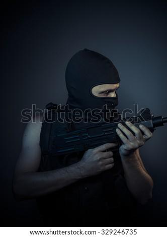 Criminal, terrorist carrying a machine gun and balaclava - stock photo