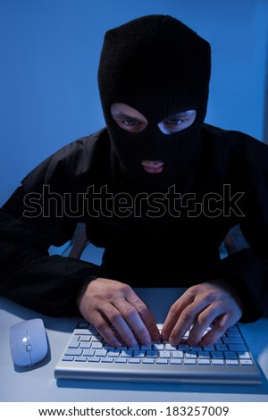 Criminal using computer to hack online account at table - stock photo