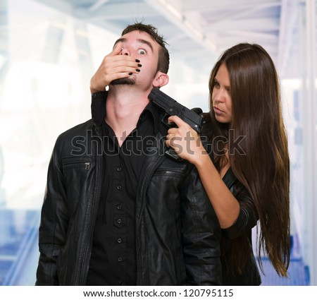 Criminal With A Gun Threatening Young Woman against an abstract background - stock photo
