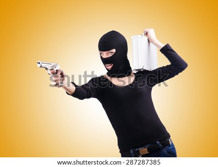 Criminal with gun against the gradient - stock photo