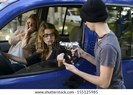 Criminal with gun robbing woman in car  - stock photo