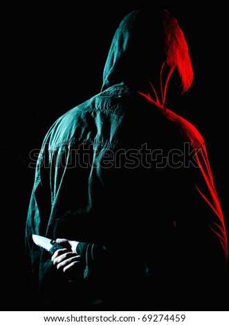 Criminal with knife behind his back - stock photo