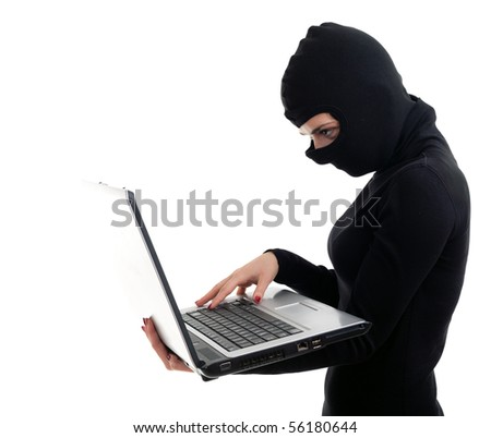 criminal woman in black clothes and balaclava with the laptop - stock photo