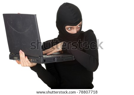 criminal woman in dark clothes and balaclava with the laptop - stock photo