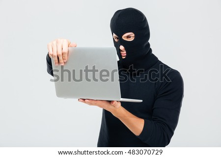 Criminal young man in balaclava standing and using laptop