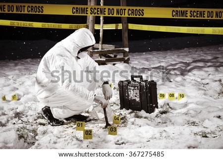 Criminologist collecting evidences on frozen winter location of crime - stock photo