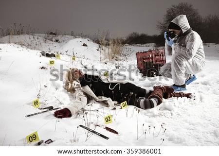 Criminologist technician photographer working on location of violent crime - stock photo