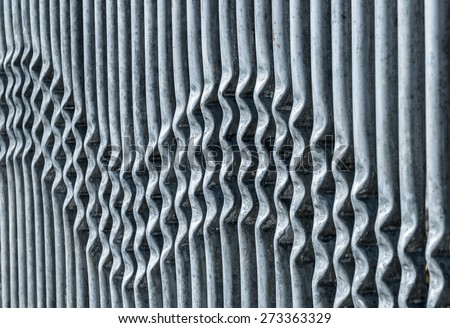 Crimped metal barrier creating a wavy pattern. - stock photo