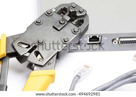 Crimping tool and network cable on white background, selective focus with shallow depth of field.