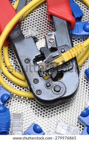 Crimping tool with network cable and connectors on metal background - stock photo