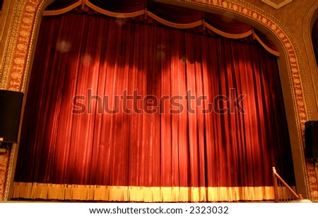 Crimson velvet stage curtain at a newly renovated Schwartz Center for the Arts in Dover, Delaware. Lens flares from the theatre lights emphasize the drama of the stage. - stock photo