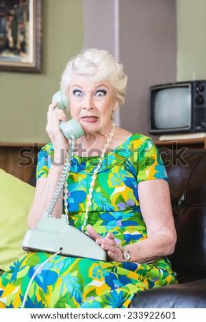 Cringing pretty senior woman in green on telephone - stock photo