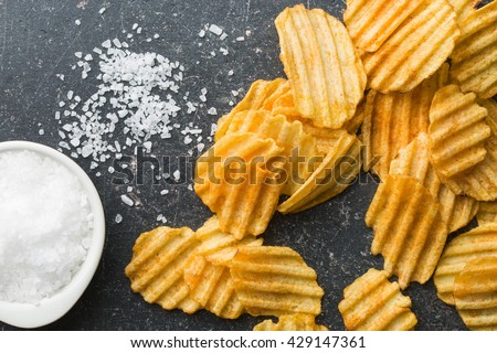 Crinkle cut potato chips on kitchen table. Tasty spicy potato chips with salt.Top view. - stock photo
