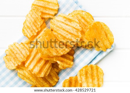 Crinkle cut potato chips on table. Tasty spicy potato chips. Top view. - stock photo