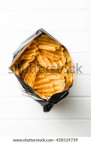 Crinkle cut potato chips on white table. Tasty spicy potato chips in bag. Top view. - stock photo