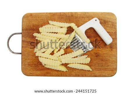 Crinkle cut raw potato chips with cutter on a wooden board isolated against white - stock photo