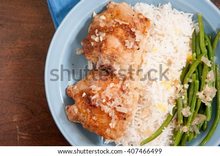 cripsy fried chicken thighs with vegetables over rice in a lemon sauce - stock photo