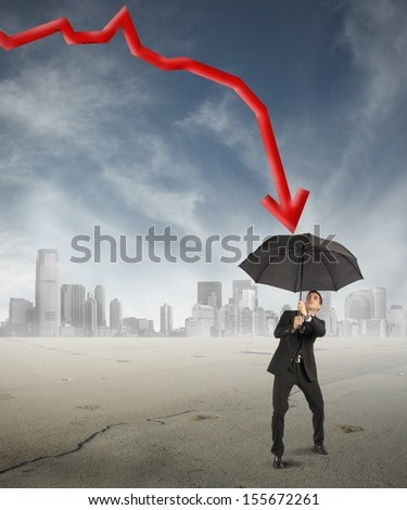 Crisis concept with the businessman who protects himself with umbrella