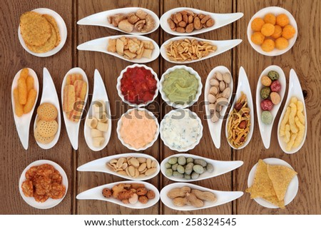Crisp and dip party snack food selection in porcelain bowls over oak background. - stock photo