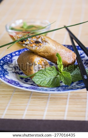 Crisp Asian spring rolls garnished with fresh herbs broken open to display the filling served with chopsticks on a blue and white plate - stock photo